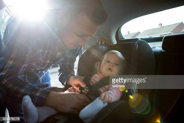 Father Putting Daughter In Safety Seat On Car Journey