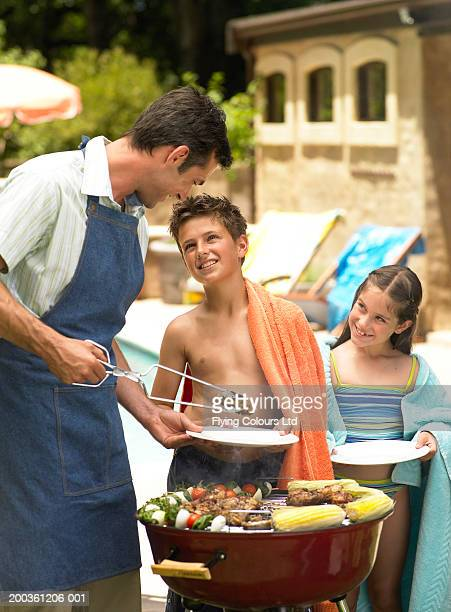 Father putting food onto children's (9-12) plates at bbq, smiling