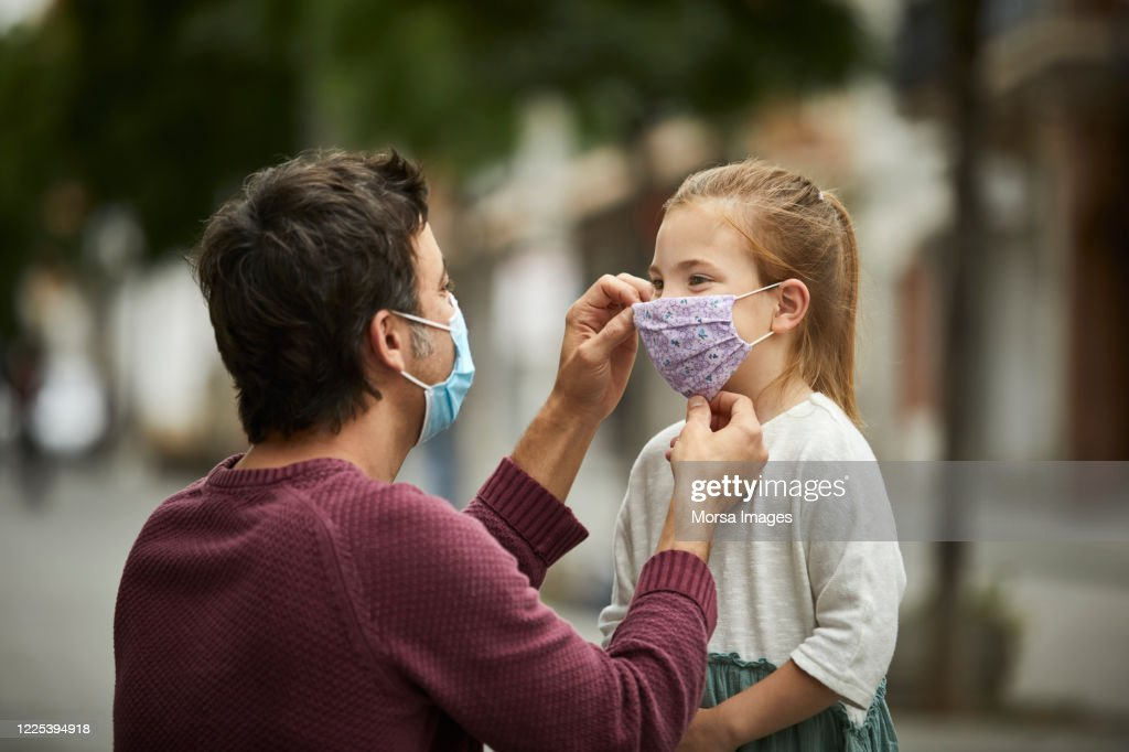 Father Putting Home Made Face Mask on Little Daughter : Stock Photo