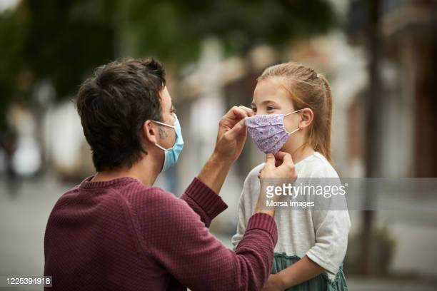 father putting home made face mask on little daughter - protective face mask stock pictures, royalty-free photos & images