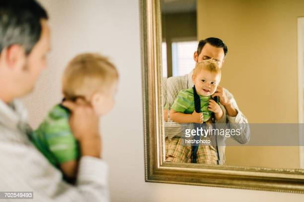 father putting neck tie on young son, reflected in mirror - heshphoto stockfoto's en -beelden