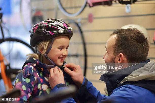 Father putting new helmet on girl in shop