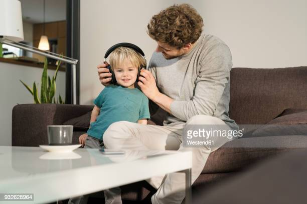 father putting on headphones on son on couch at home - genderblend stock pictures, royalty-free photos & images