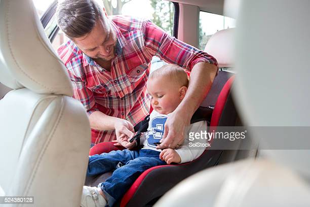 Father Putting Son In Safety Seat On Car Journey
