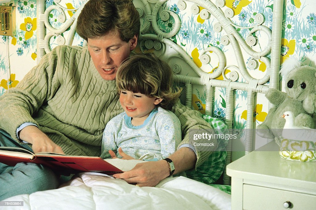 Father reading a book to daughter in bed : Stockfoto