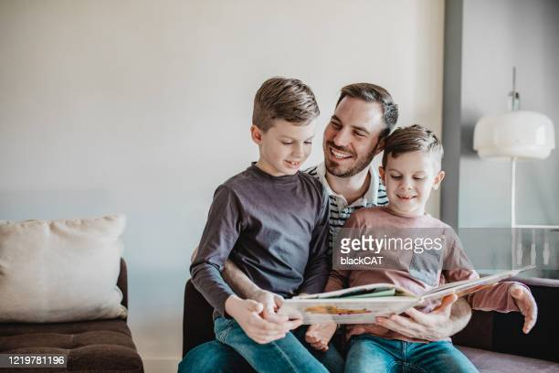 father reading a book to her sons - genderblend stock pictures, royalty-free photos & images