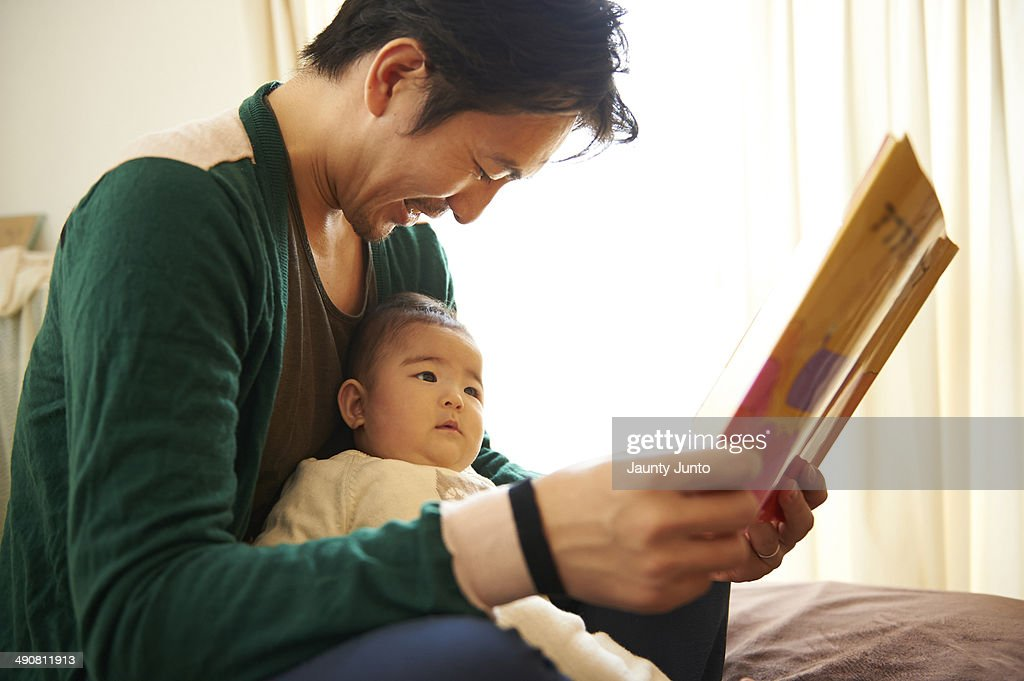 Father reading a picture book for his baby : Stock Photo