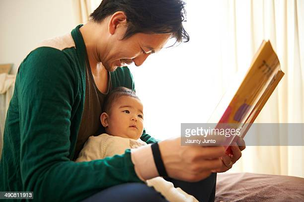 father reading a picture book for his baby - 主夫 ストックフォトと画像