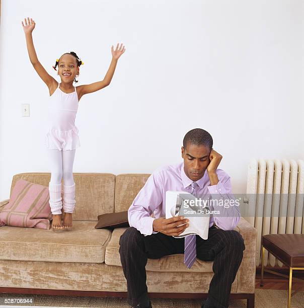 Father Reading and Daughter Jumping on Couch