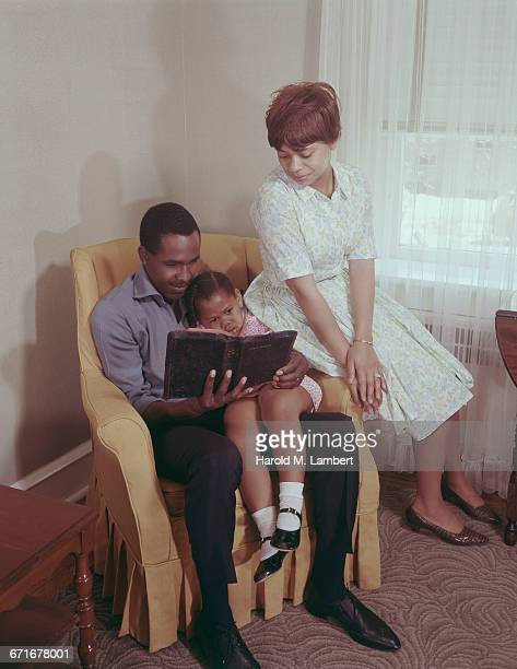 father reading bible while daughter sitting on lap and wife besides him  - {{relatedsearchurl(carousel.phrase)}} ストックフォトと画像