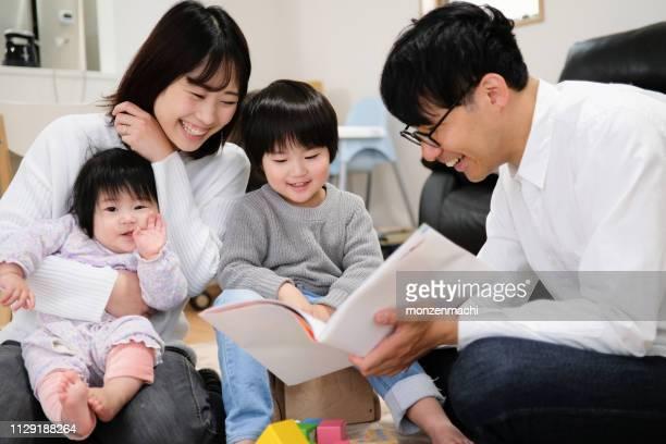 父は、子供や赤ちゃんに本を読んで - 4人 ストックフォトと画像