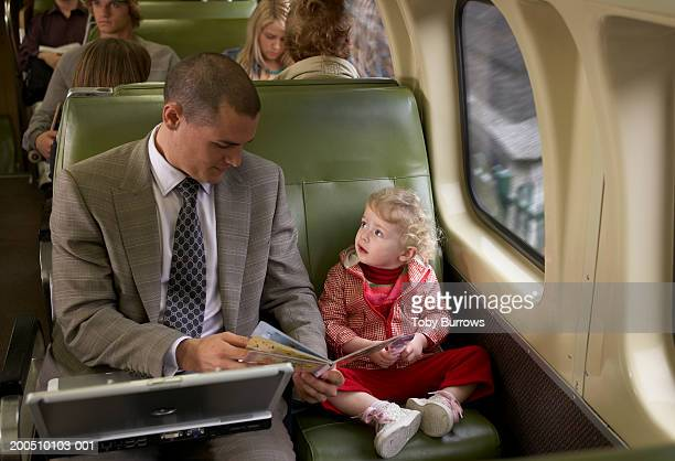 Father reading book to daughter (18-24 months) on train