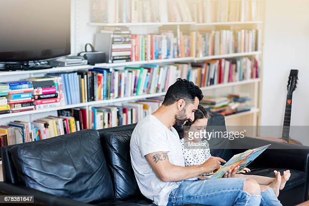 Father reading book to daughter while sitting on sofa against bookshelf at home