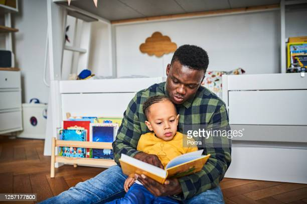 father reading book to son at home - stay at home father stock pictures, royalty-free photos & images