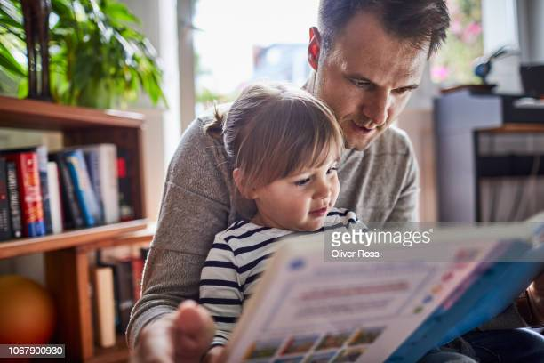 father reading book with daughter at home - vater stock-fotos und bilder
