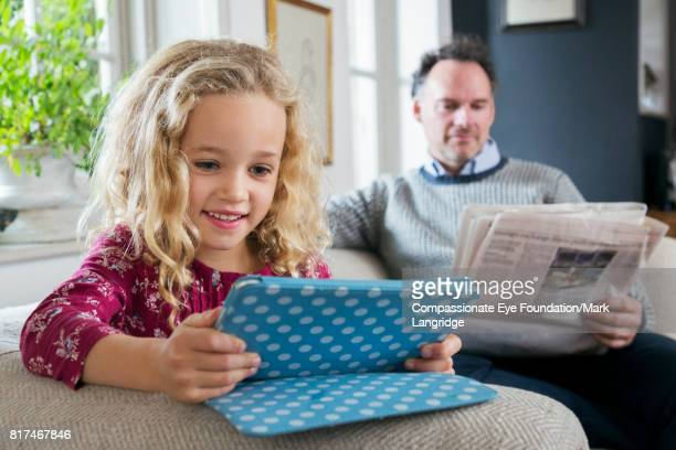 Father reading newspaper and daughter using digital tablet in living room