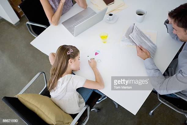 Father reading newspaper at table while daughter draws