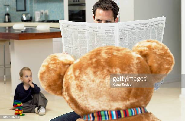 Father reading newspaper behind teddy bear
