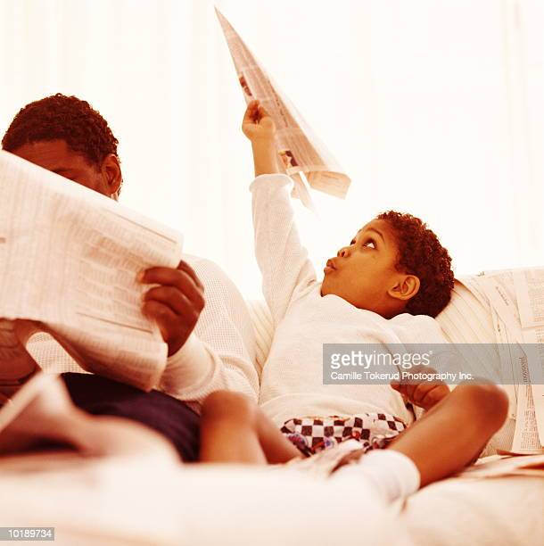 Father reading newspaper, boy (5 years) playing with paper plane