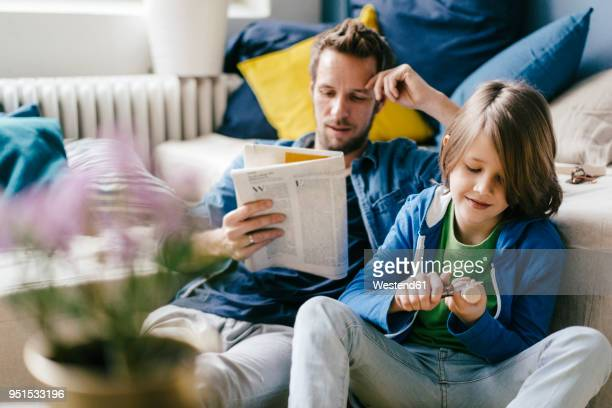 Father reading newspaper while son carving at home