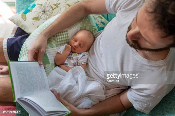 father reading paper book with baby on lap - paternity leave stock pictures, royalty-free photos & images