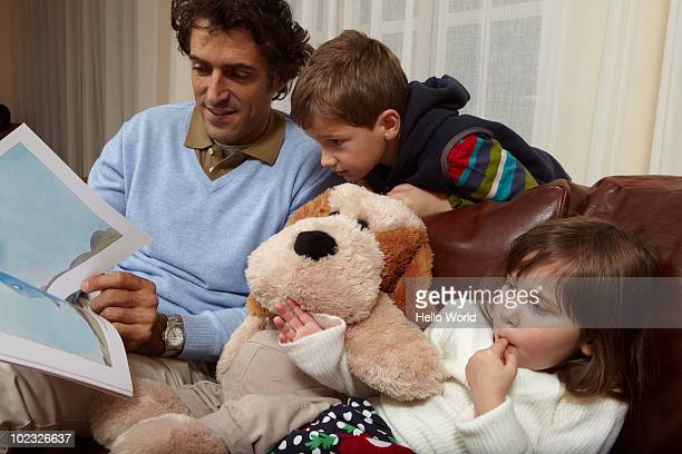Father reading picture book to kids on couch
