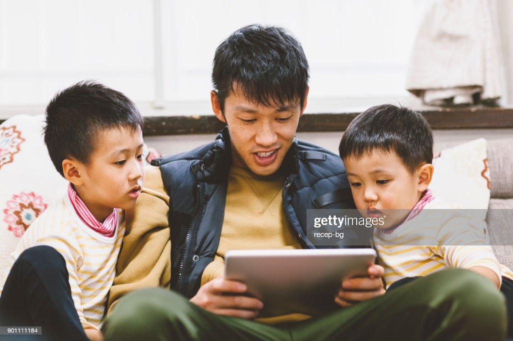 デジタル タブレットの彼の息子に父の読んでストーリー : ストックフォト