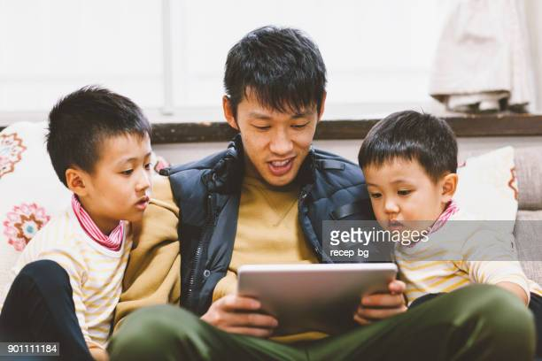 Father Reading Stories On Digital Tablet For His Sons