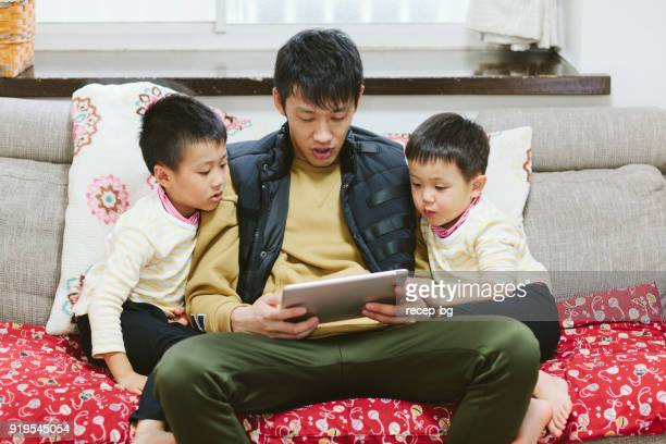 father reading stories on digital tablet for his sons - storyteller stock pictures, royalty-free photos & images