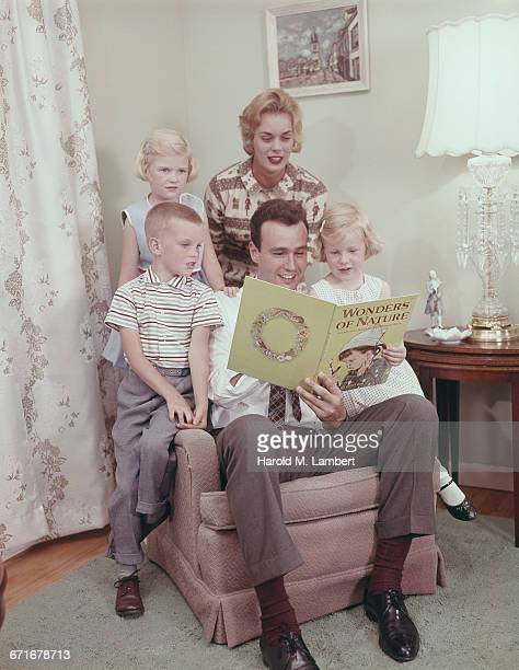 father reading story book while family listening  - neckwear stock pictures, royalty-free photos & images
