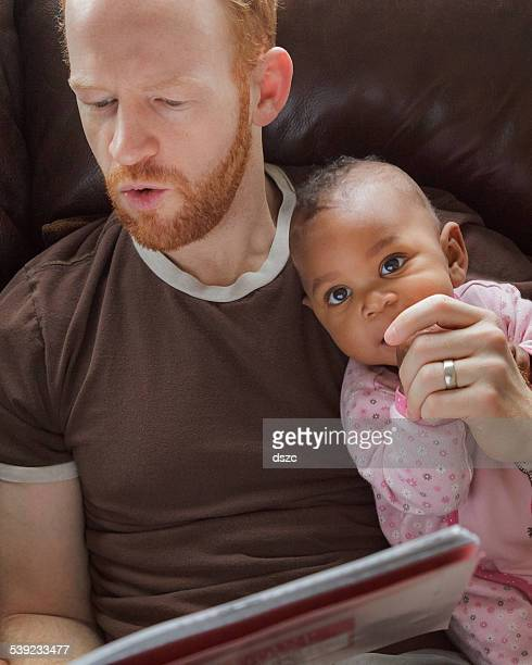 father reading storybook, baby daughter, adopted african descent, little girl - black ginger baby stock photos and pictures