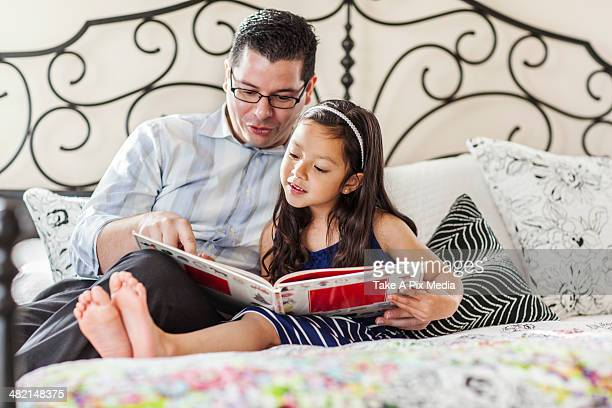 Father reading to daughter on bed