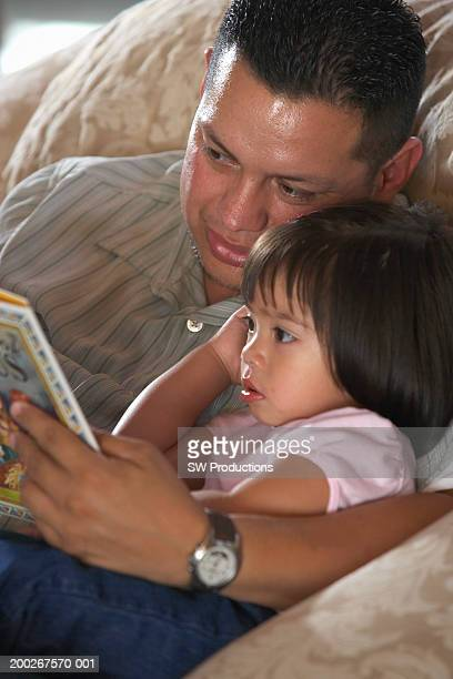 Father reading to toddler daughter (21-24 months), close-up