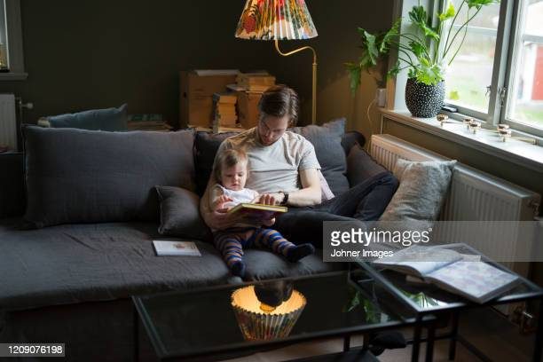 father reading with son - paternity leave stock pictures, royalty-free photos & images