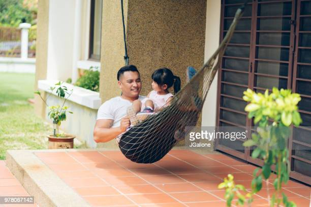 Father relaxing in a hammock with his daughter