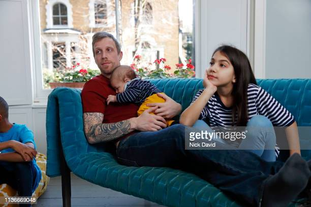 father relaxing with children on sofa watching tv - stepfamily stock photos and pictures