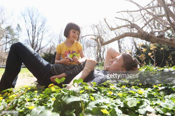 A father relaxing with his daughter in a park