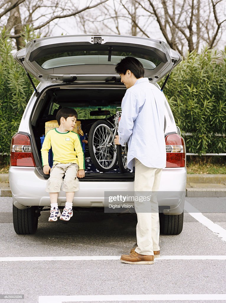 Father Removing His Son's Bicycle From the Back of a Car : Stock Photo