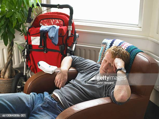 Father resting in armchair by pram, eyes closed