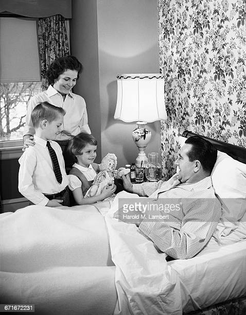 father resting in bed and family standing beside - {{ contactusnotification.cta }} stockfoto's en -beelden