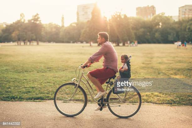 father riding a bicycle with his son on a baby seat - bicycle stock pictures, royalty-free photos & images
