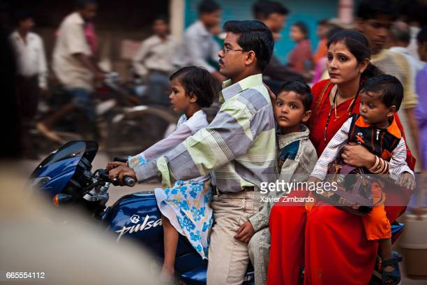 A father riding a motorcycle transports his family a mother with three children along a busy street on October 12 2005 at Varanasi Uttar Pradesh India