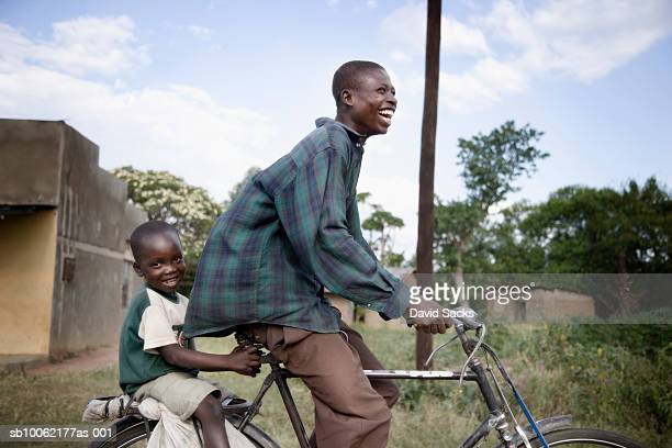 father riding bicycle and son (4-5) sitting on rear pannier, smiling, side view - developing countries stock pictures, royalty-free photos & images