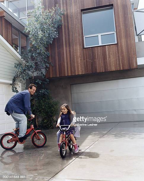 father riding bikes daughters (4-8) in driveway - driveway stock pictures, royalty-free photos & images