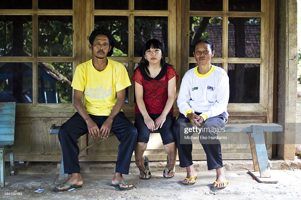 Father Rohmad Saputro, Erwiana Sulistyaningsih and mother Suratmi pose for a family photo on May 27, 2014 in Ngawi, Indonesia. Erwiana has been voted one of 100 most influential people awarded by TIME magazine. She was abused by her employer in Hong Kong. Since returning to Indonesia, her story has spread globally and helped to raise awareness about the treatment of Asian migrant workers. Migrant workers in Hong Kong hold regular demonstrations to fight violence against workers. Currently Erwiana is fighting her former employer in a high profile court case.