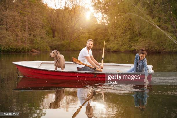 Father rowing boat with daughter and Weimaraner on lake against trees