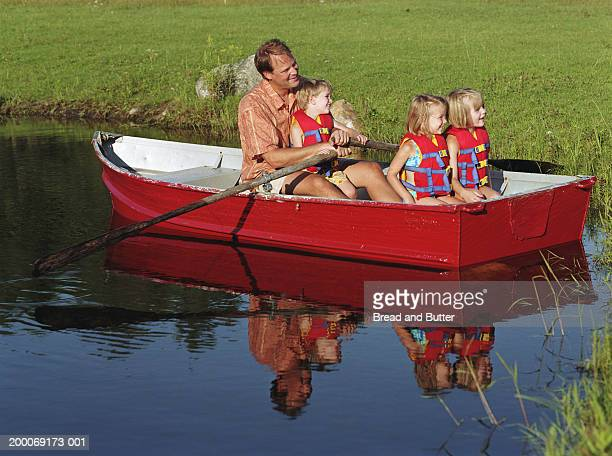 Father rowing boat with three children (3-6)