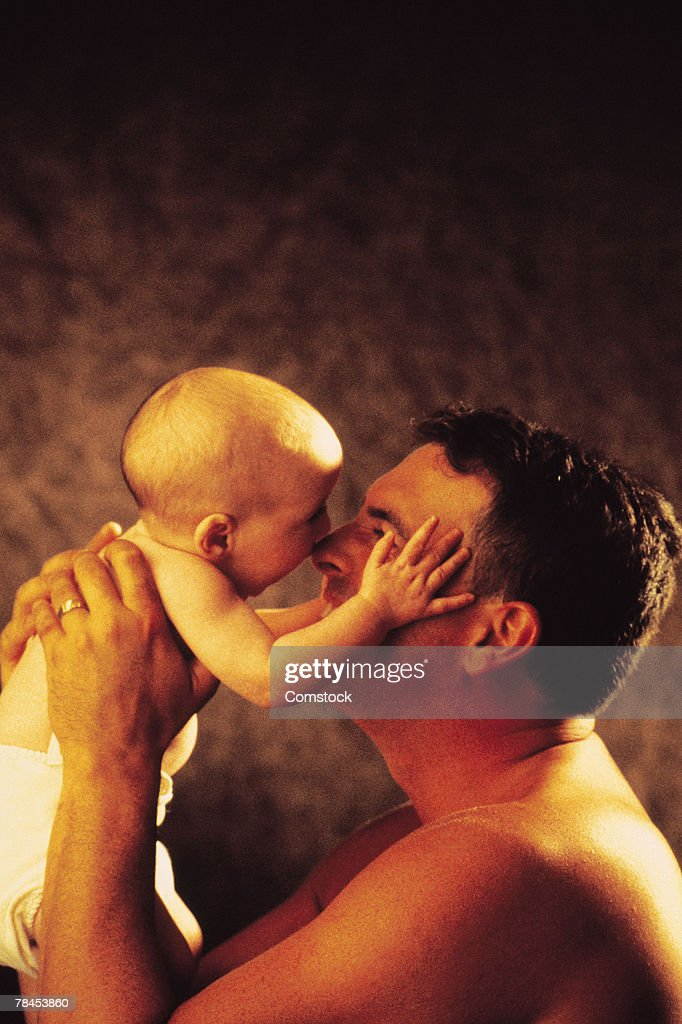 Father rubbing noses with baby : Stockfoto