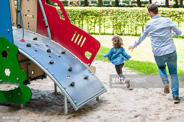 Father running with daughter on playground