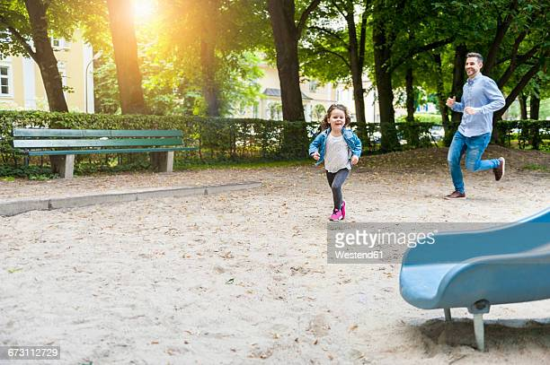 father running with daughter on playground - chasing stock pictures, royalty-free photos & images